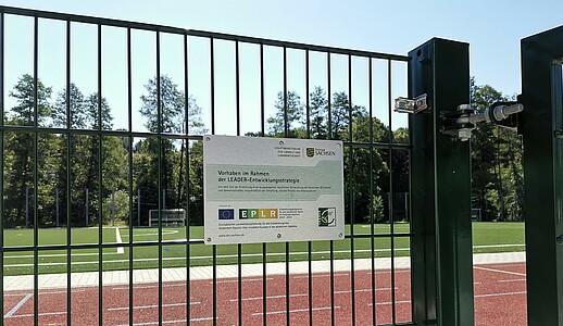 Blick durch den Zaun auf die neu errichtete Sportanlage, am Zaun ist die LEADER-Infotafel angebracht.