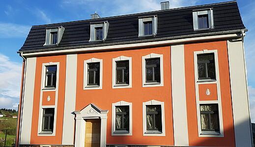 Frisch gestrichene Fassade des sanierten Wohnhauses.