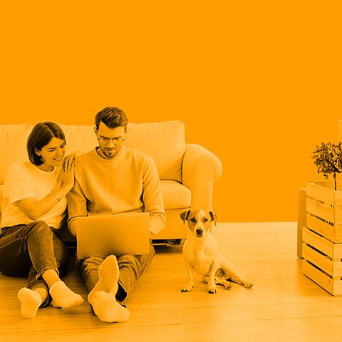 Mann und Frau vor einem Sofa schauen gemeinsam auf ein Notebook.