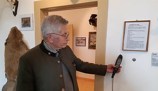 Ein älterer Mann benutzt den Audioguide.