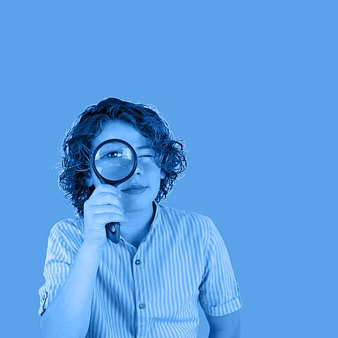 Eine junge Frau schaut durch eine Lupe.