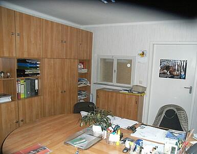 Büroraum mit Schreibtisch und Schrank.